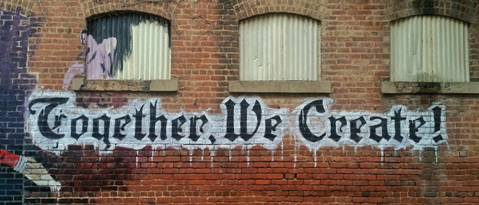 Graffiti on building saying Together We Create
