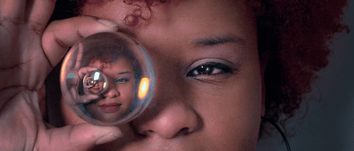 Woman looking through a crystal ball making marketing predictions